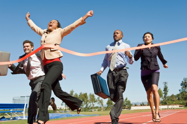 Woman Crossing The Finish Line With Colleagues Running